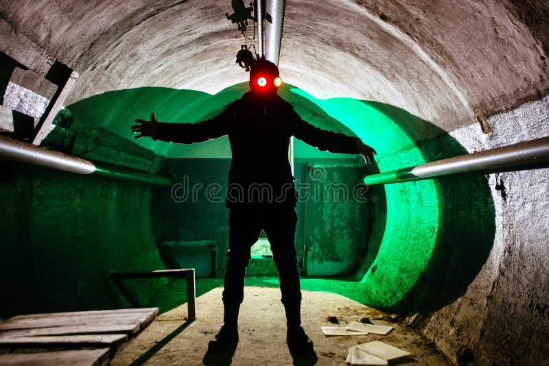 Ανατριχιαστική σιλουέτα του ανθρώπου σε μάσκα με λαμπερά μάτια σε σκοτεινό εγκαταλελειμμένο καταφύγιο Τρόμος για την ιδέα των μαν στοκ εικόνα με δικαίωμα ελεύθερης χρήσης