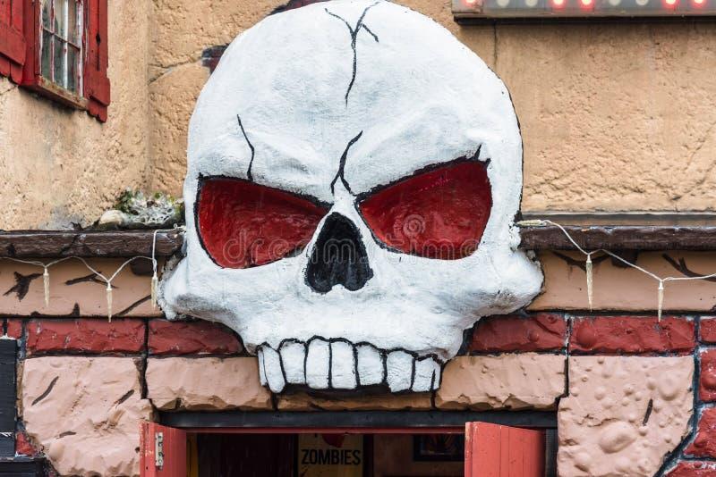 Ανατριχιαστικό κρανίο επάνω από την είσοδο ενός συχνασμένου σπιτιού στοκ φωτογραφίες με δικαίωμα ελεύθερης χρήσης