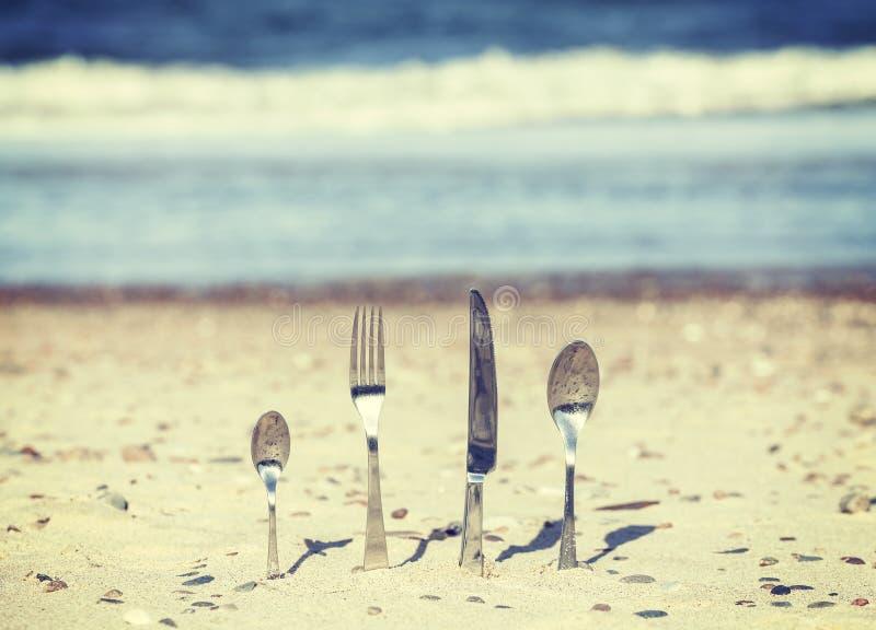 Αναδρομικά τονισμένα μαχαιροπήρουνα που κολλιούνται στην άμμο στην παραλία στοκ φωτογραφίες με δικαίωμα ελεύθερης χρήσης