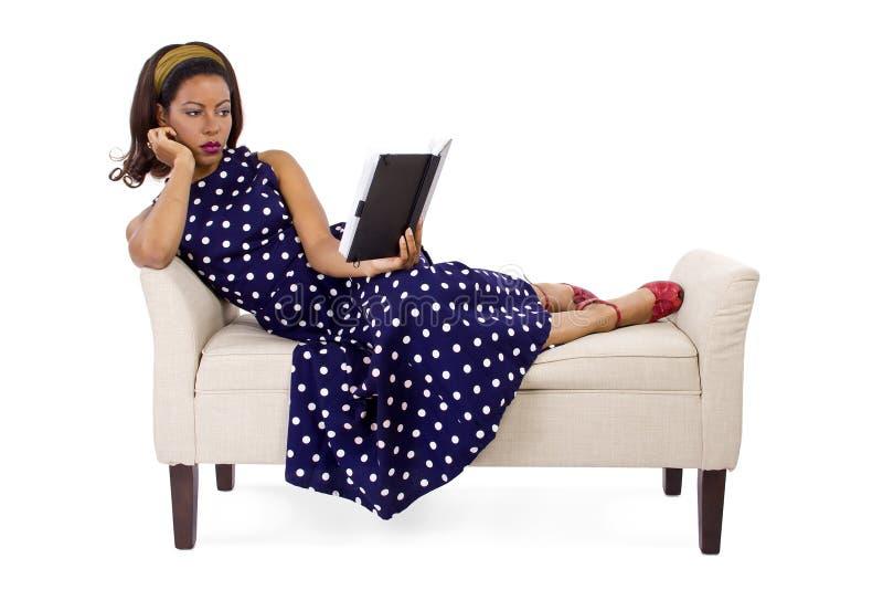 Αναδρομική γυναίκα που διαβάζει ένα βιβλίο στοκ εικόνα