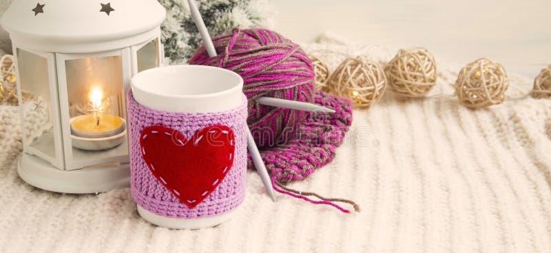 Αναδρομική διακόσμηση Χριστουγέννων με το φλυτζάνι, το φανάρι κεριών και το πλέξιμο στοκ φωτογραφίες