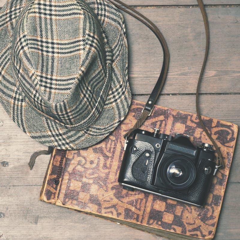 Αναδρομική κάμερα με το εκλεκτής ποιότητας καπέλο ρεπούμπλικων και λεύκωμα φωτογραφιών στο ξύλινο β στοκ εικόνες