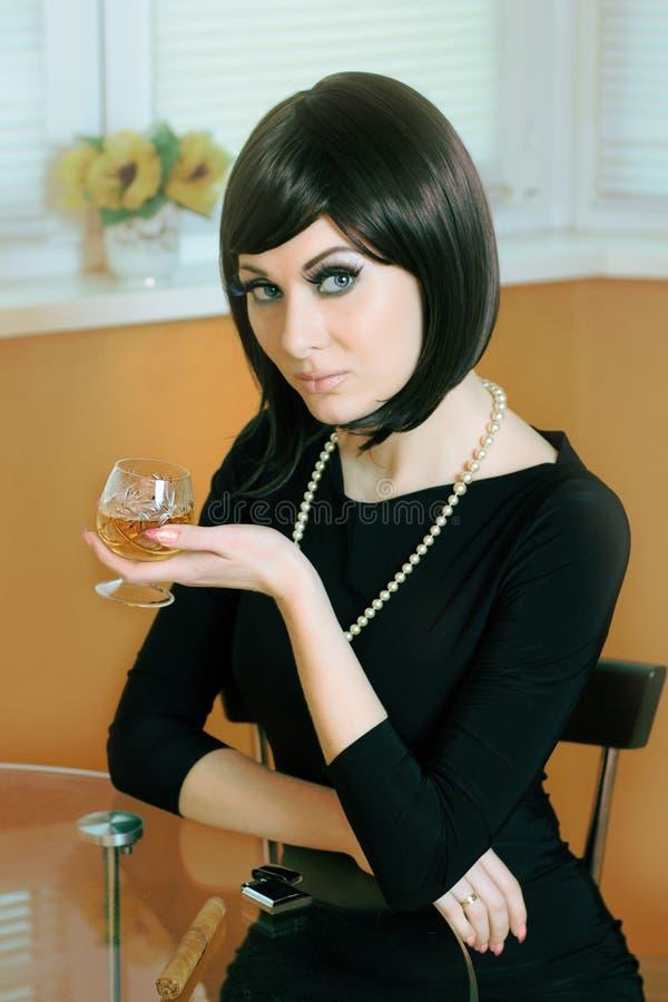 Γυναίκα με το ποτήρι του κονιάκ στοκ φωτογραφία