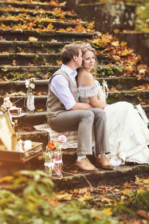 Αναδρομική συνεδρίαση γαμήλιων ζευγών ύφους στα βήματα πετρών και αγκάλιασμα στο δάσος φθινοπώρου, που περιβάλλεται από την όμορφ στοκ εικόνα