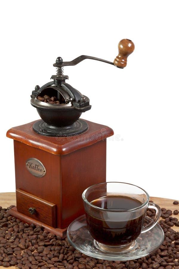 Αναδρομικός χειρωνακτικός μύλος καφέ στα ψημένα φασόλια καφέ με ένα φλιτζάνι του καφέ στοκ φωτογραφίες