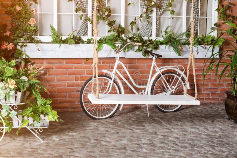 Αναδρομικό εκλεκτής ποιότητας ποδήλατο μπροστά από τον παλαιό τουβλότοιχο και ταλάντευση στον κήπο στοκ εικόνες