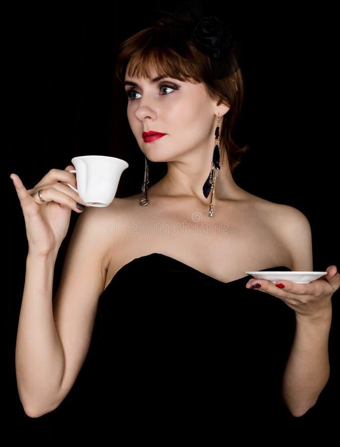 Αναδρομικό θηλυκό πρότυπο ομορφιάς με το επαγγελματικό makeup, τον καφέ κατανάλωσης ή το τσάι εκλεκτής ποιότητας γυναίκα μόδας σε στοκ εικόνες