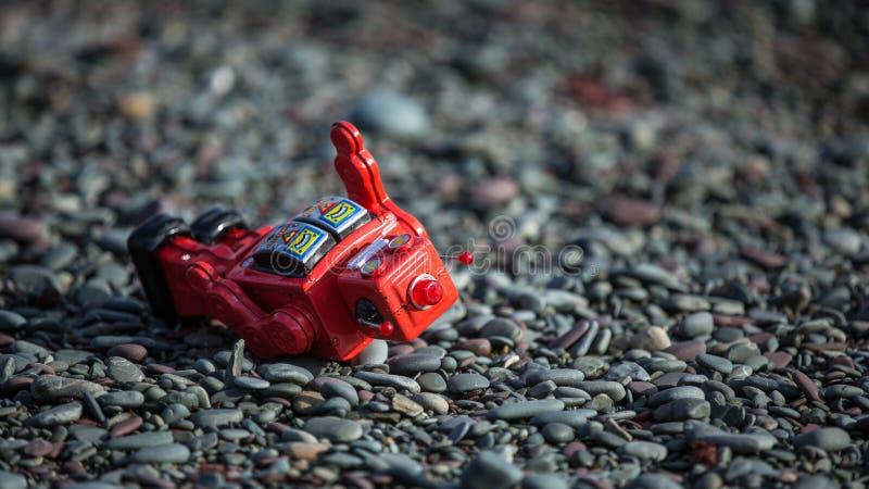 Αναδρομικό κόκκινο ρομπότ αφορημένος τους βράχους στοκ εικόνα με δικαίωμα ελεύθερης χρήσης