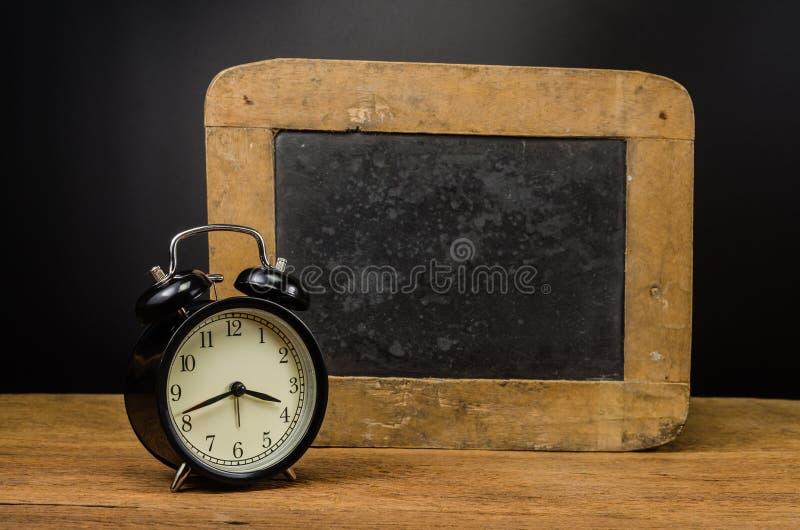 Αναδρομικό ξυπνητήρι και παλαιά πλάκα στοκ φωτογραφία με δικαίωμα ελεύθερης χρήσης