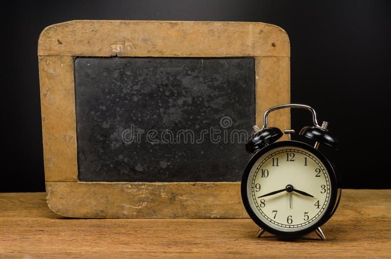 Αναδρομικό ξυπνητήρι και παλαιά πλάκα στοκ εικόνες