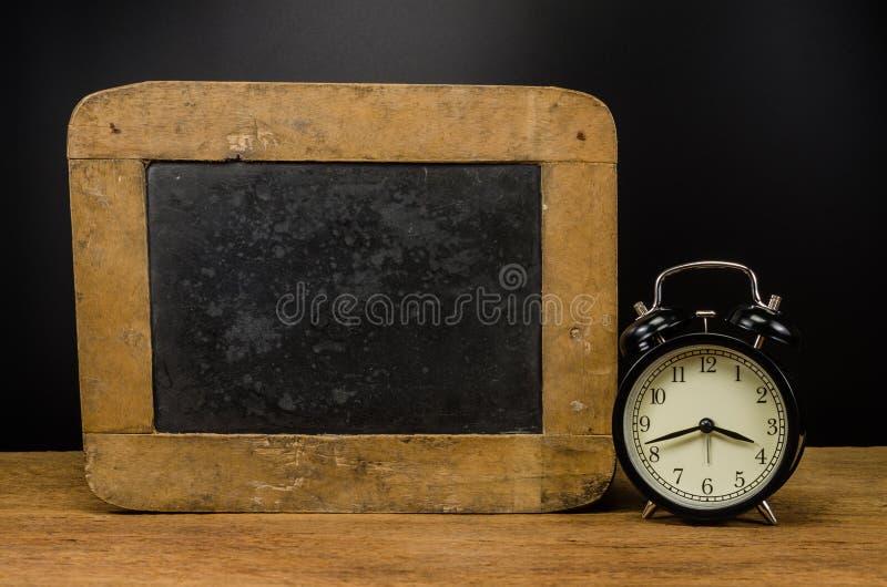 Αναδρομικό ξυπνητήρι και παλαιά πλάκα στοκ φωτογραφία