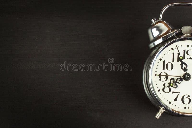 Αναδρομικό ξυπνητήρι μετάλλων σε ένα μαύρο ξύλινο υπόβαθρο τα μάτια ανοίγουν το σας Reveille ξυπνήστε τοποθετήστε το κείμενο στοκ φωτογραφίες με δικαίωμα ελεύθερης χρήσης