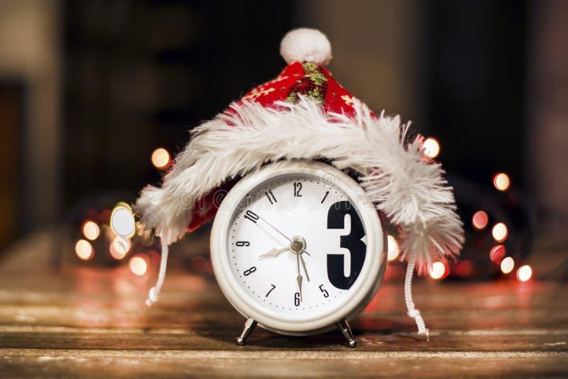 Αναδρομικό ξυπνητήρι με το κόκκινο καπέλο Χριστουγέννων στοκ φωτογραφίες