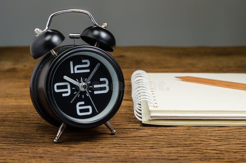 Αναδρομικό ξυπνητήρι με το σημειωματάριο στοκ φωτογραφία με δικαίωμα ελεύθερης χρήσης