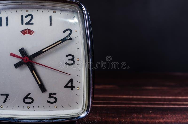 Αναδρομικό ξυπνητήρι στο ξύλινο υπόβαθρο πινάκων στοκ φωτογραφία