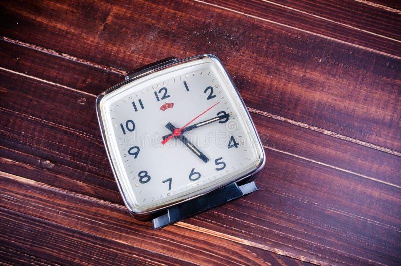 Αναδρομικό ξυπνητήρι στο ξύλινο υπόβαθρο πινάκων στοκ εικόνες