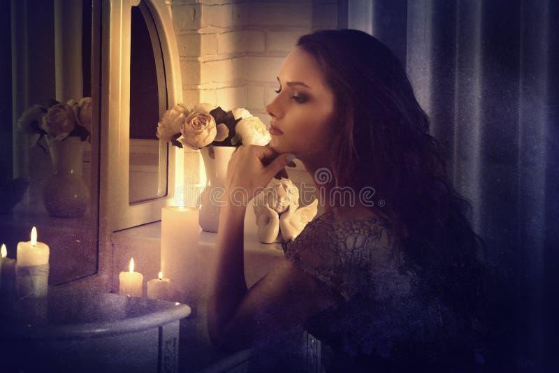 αναδρομικό ύφος Το κορίτσι κάθεται μπροστά από έναν καθρέφτη στοκ φωτογραφία