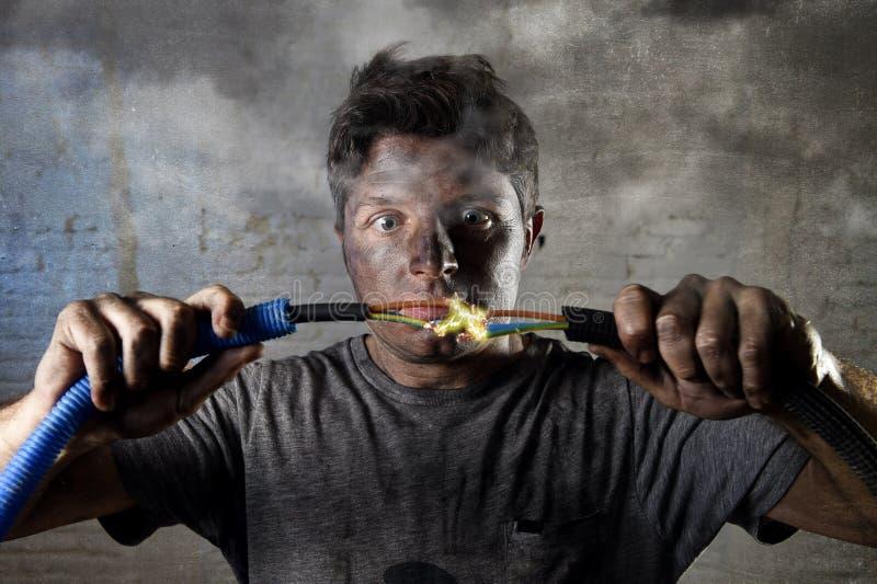 Ανεκπαίδευτο ενώνοντας καλώδιο ατόμων που υφίσταται το ηλεκτρικό ατύχημα με τη βρώμικη μμένη έκφραση κλονισμού προσώπου στοκ εικόνες