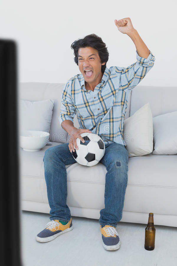 Ανεμιστήρας ποδοσφαίρου ενθαρρυντικός προσέχοντας τη TV στοκ φωτογραφία με δικαίωμα ελεύθερης χρήσης