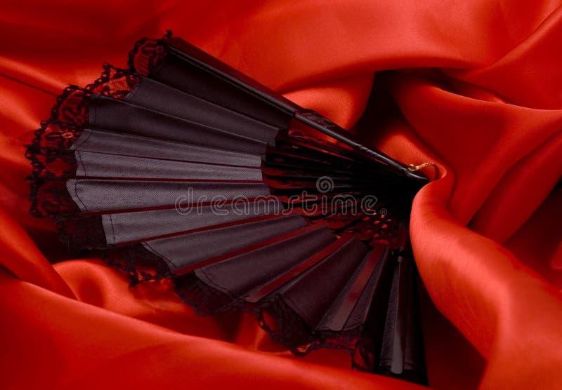 Ανεμιστήρας στο κόκκινο σατέν στοκ εικόνα