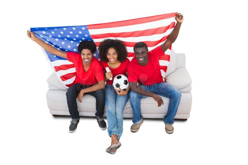 Ανεμιστήρες αμερικανικού ποδοσφαίρου στο κόκκινο στον καναπέ στοκ εικόνα