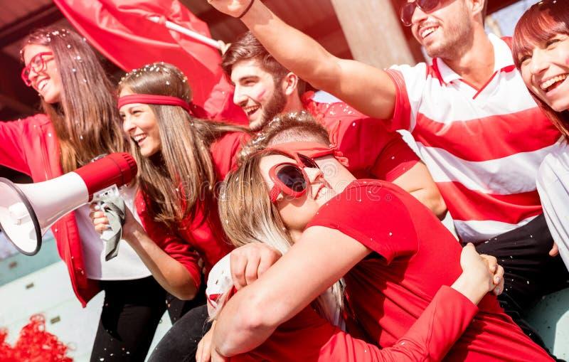 Ανεμιστήρες οπαδών ποδοσφαίρου φίλων που αγκαλιάζουν ο ένας τον άλλον που προσέχει socc στοκ εικόνες