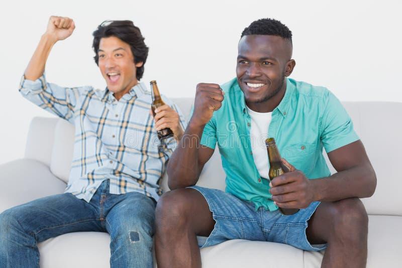 Ανεμιστήρες ποδοσφαίρου ενθαρρυντικοί προσέχοντας τη TV στοκ εικόνες