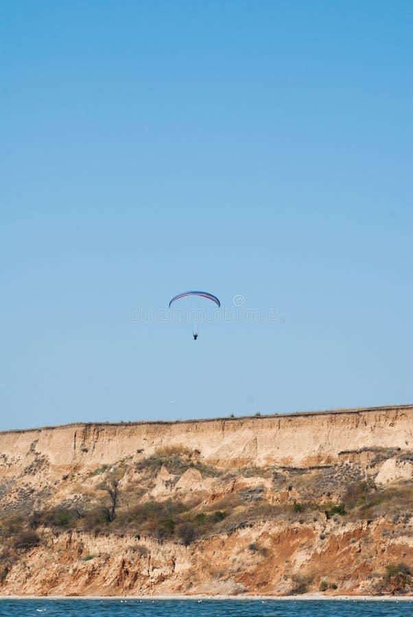 Ανεμόπτερο που αιωρείται πέρα από τον απότομο βράχο και το τοπίο της θάλασσας, που πετούν στα ύψη στον αέρα, το άκρο και την ψυχα στοκ εικόνες