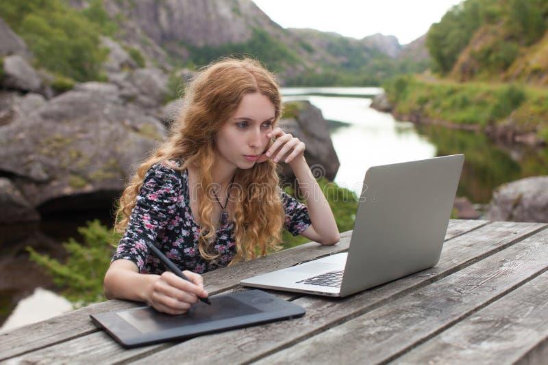 Ανεξάρτητο κορίτσι που εργάζεται στο lap-top στα όμορφα τοπία στοκ εικόνες