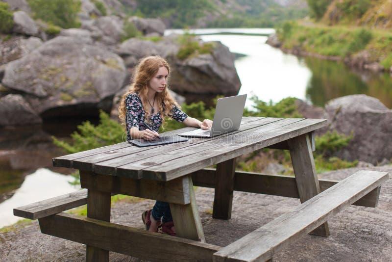 Ανεξάρτητο κορίτσι που εργάζεται στο lap-top στη φύση στοκ εικόνα με δικαίωμα ελεύθερης χρήσης