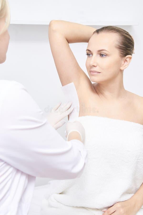 Ανεπιθύμητο epilation κεριών τρίχας 15 woman young cosmetology διαδικασία επεξεργασίας σαλονιών Εγχώριο κήρωμα στοκ φωτογραφία με δικαίωμα ελεύθερης χρήσης