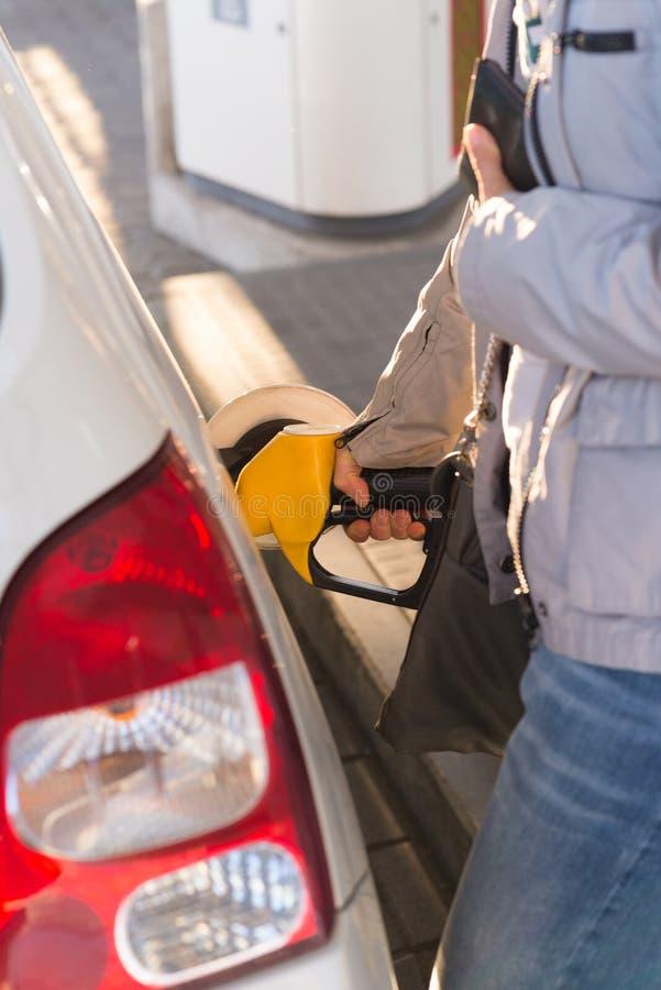 Ανεφοδιάζοντας σε καύσιμα δεξαμενή αυτοκινήτων γυναικών και κράτημα του πορτοφολιού στοκ εικόνα