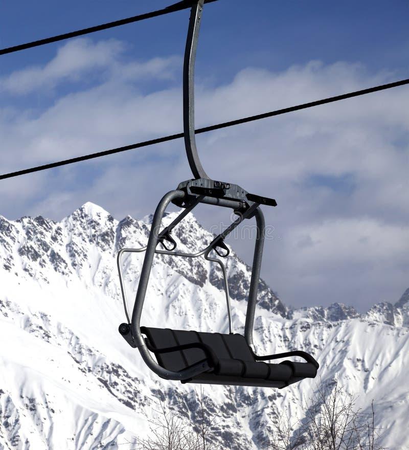 Ανελκυστήρας εδρών στα χιονώδη βουνά στη συμπαθητική ημέρα ήλιων στοκ εικόνες