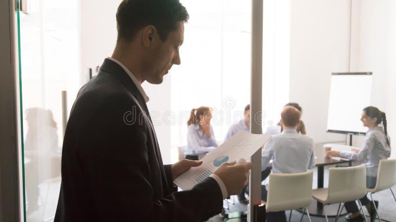 Ανησυχημένη αρσενική γραφική εργασία ανάγνωσης παρουσιαστών πριν από την παρουσίαση στοκ εικόνες