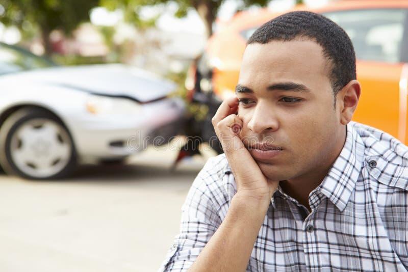 Ανησυχημένη αρσενική συνεδρίαση οδηγών με το αυτοκίνητο μετά από το τροχαίο ατύχημα στοκ φωτογραφία με δικαίωμα ελεύθερης χρήσης