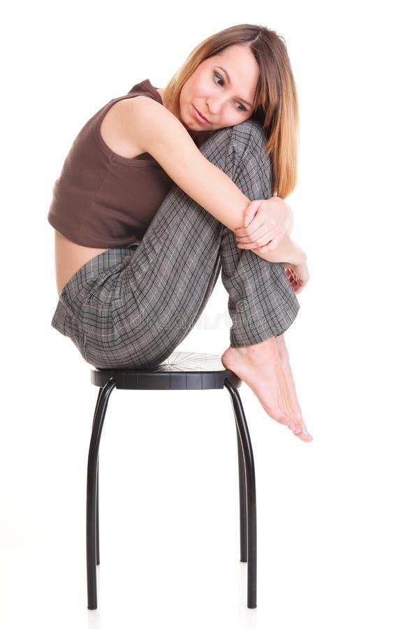 Ανησυχημένη και φοβισμένη νέα συνεδρίαση γυναικών στην καρέκλα. Απομονωμένος στοκ φωτογραφίες