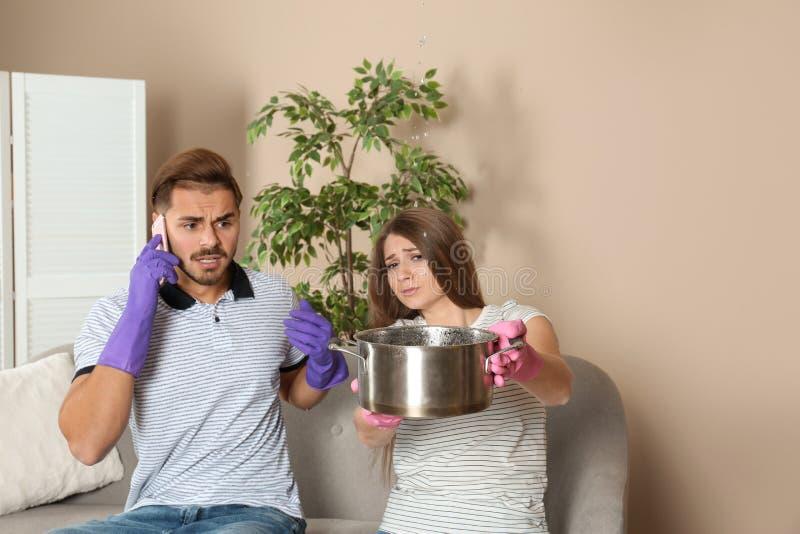 Ανησυχημένη νέα γυναίκα που συλλέγει τη διαρροή νερού από το ανώτατο όριο ενώ ο σύζυγός της που καλεί τον υδραυλικό στοκ εικόνα
