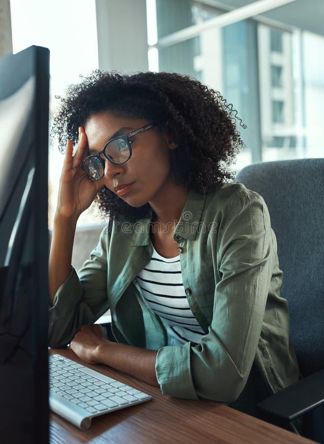 Ανησυχημένη νέα επιχειρηματίας που εξετάζει τον υπολογιστή στοκ εικόνες