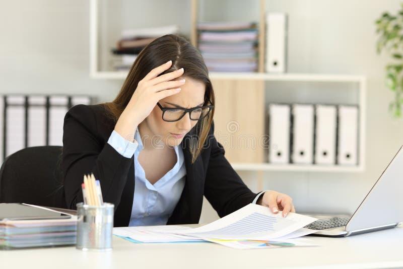 Ανησυχημένος ανώτερος υπάλληλος που ελέγχει ένα αρνητικό διάγραμμα στοκ φωτογραφίες