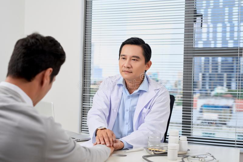 Ανησυχημένος ασθενής με το γιατρό του στο ιατρικό γραφείο στοκ εικόνα