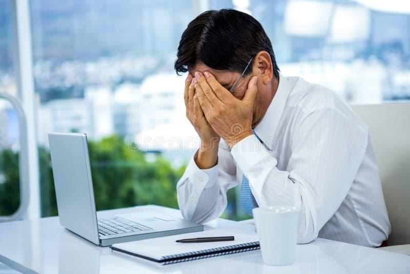 Ανησυχημένος επιχειρηματίας που εργάζεται στο γραφείο του στοκ εικόνες με δικαίωμα ελεύθερης χρήσης