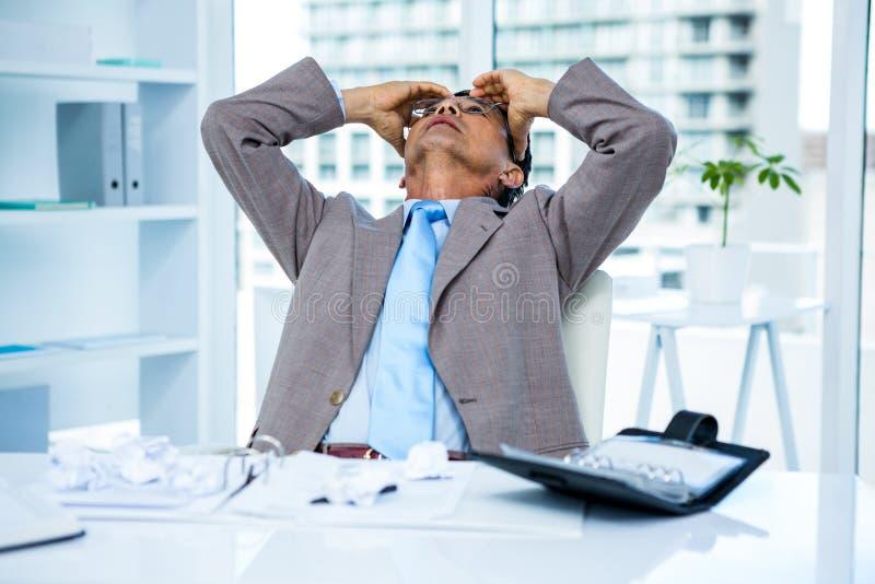 Ανησυχημένος επιχειρηματίας που εργάζεται στο γραφείο του στοκ εικόνες
