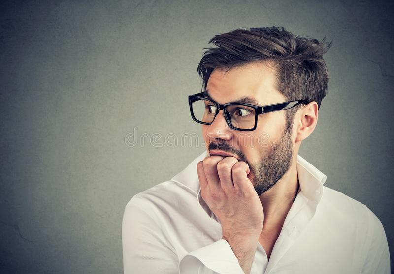 Ανησυχημένο ανήσυχο άτομο που δαγκώνει τα νύχια του που κοιτάζουν στην πλευρά στοκ εικόνες
