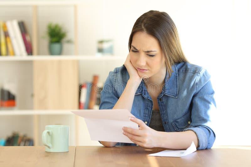 Ανησυχημένο θηλυκό που διαβάζει μια επιστολή σε έναν πίνακα στο σπίτι στοκ φωτογραφία με δικαίωμα ελεύθερης χρήσης