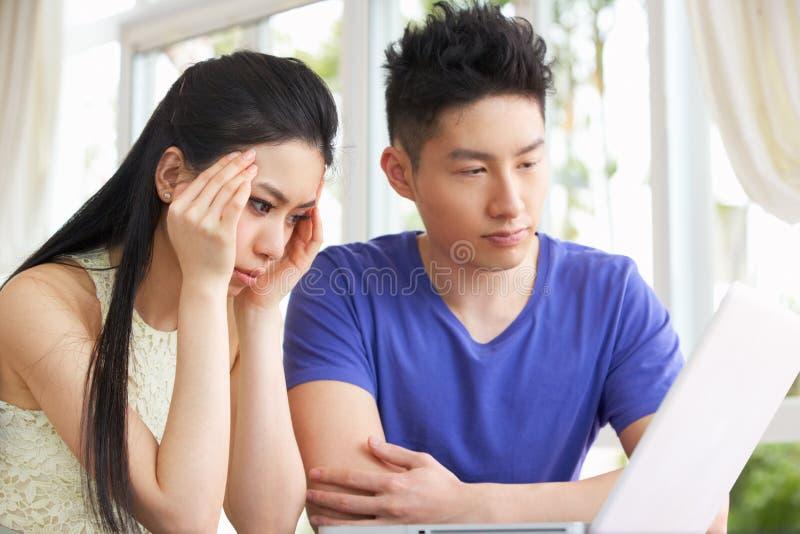 Ανησυχημένο νέο κινεζικό ζεύγος που χρησιμοποιεί το lap-top στοκ εικόνες με δικαίωμα ελεύθερης χρήσης