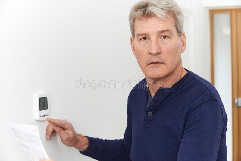 Ανησυχημένο ώριμο άτομο με το Μπιλ που γυρίζει κάτω την κεντρική θέρμανση θερμο στοκ εικόνα με δικαίωμα ελεύθερης χρήσης