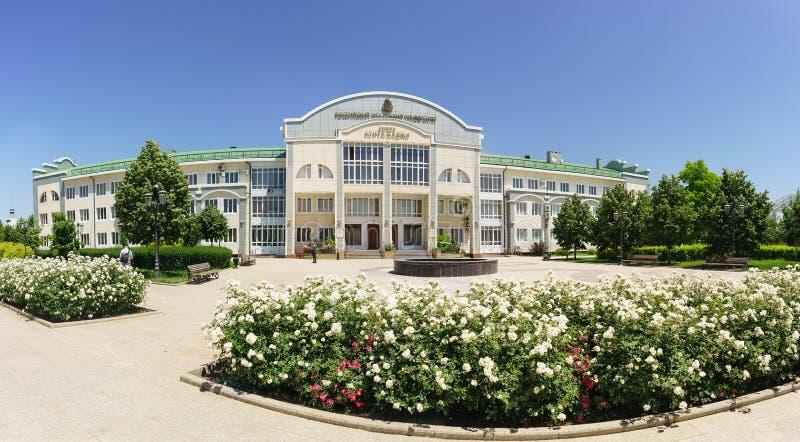 Ανθίζοντας άσπρα τριαντάφυλλα κοντά στο ισλαμικό πανεπιστήμιο Kunta Haji της Ρωσίας r Σημάδι με το όνομα στα ρωσικά: στοκ φωτογραφία