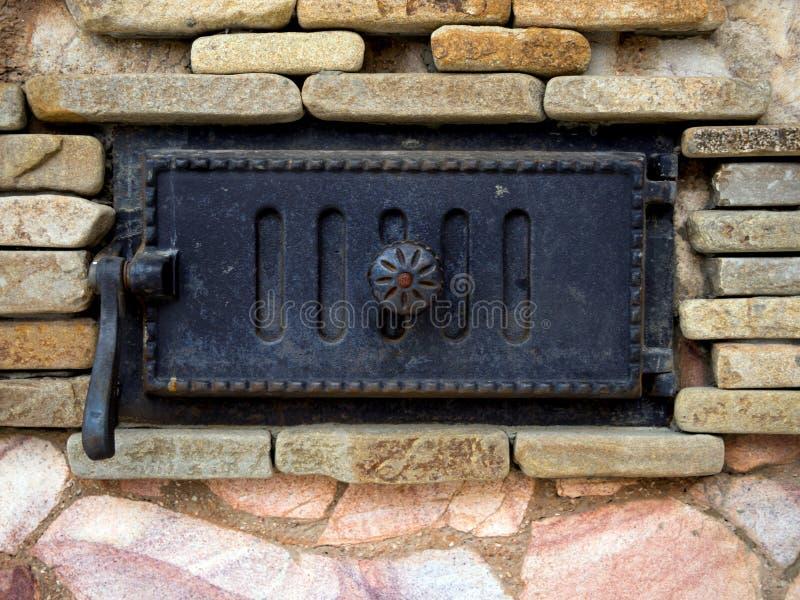 Ανθισμένη σόμπα πετρών με μια διακοσμητική πόρτα χυτοσιδήρου στοκ εικόνες