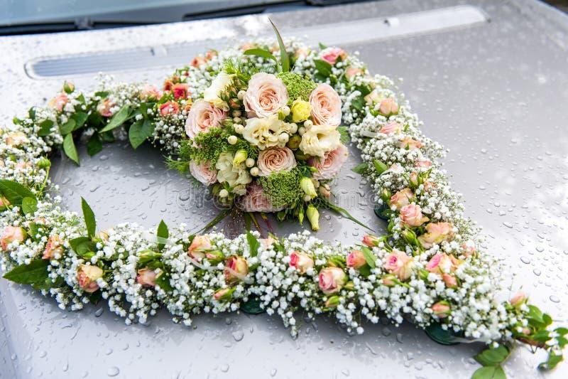 Ανθοδέσμη γαμήλιων λουλουδιών στη μορφή δαπέδων τζακιού στο καπό αυτοκινήτων στοκ φωτογραφία
