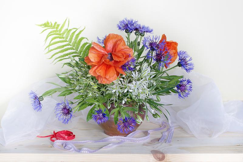 Ανθοδέσμη με τις παπαρούνες, cornflowers, snowdrops σε ένα βάζο σε ένα άσπρο υπόβαθρο στοκ εικόνες με δικαίωμα ελεύθερης χρήσης
